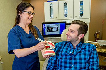Staff showing patient procedure using model of teeth.