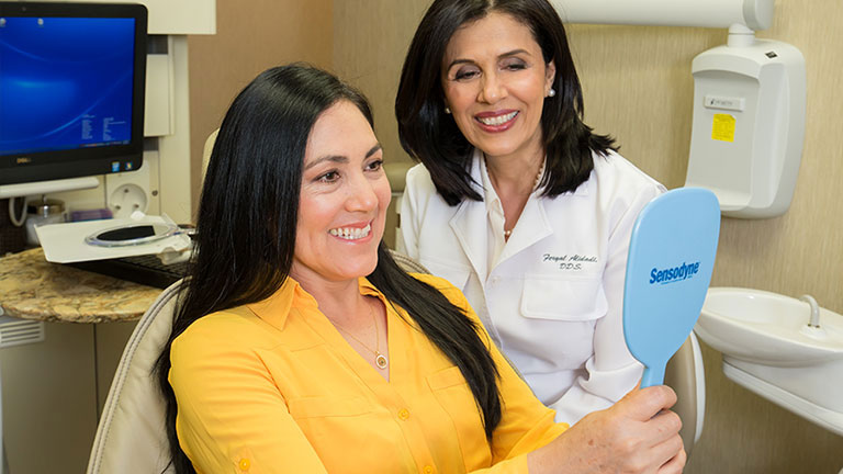 Patient looking at her beautiful new smile in a handheld mirror.