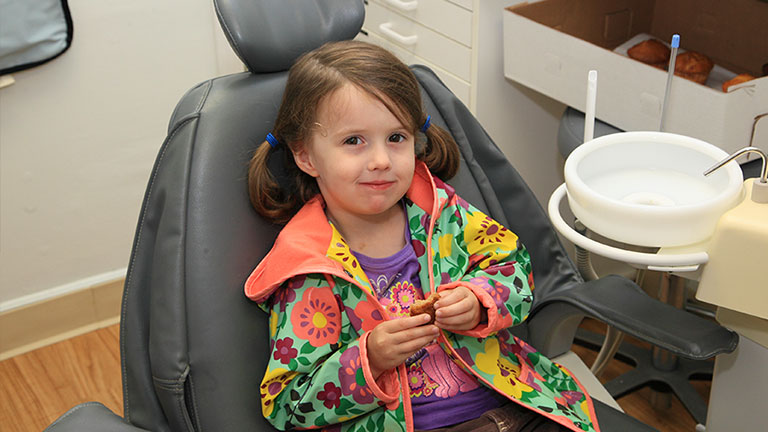 Child patient enjoying a muffin.