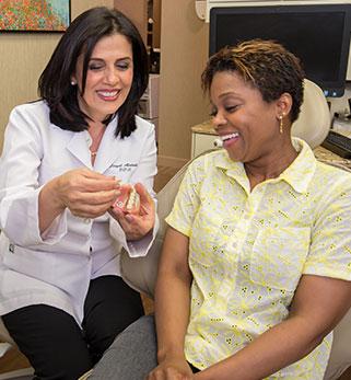 Doctor Alidadi showing patient a model of teeth.