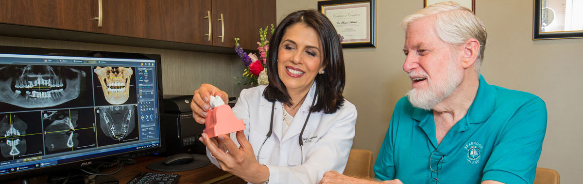 Doctor Alidadi explaining a procedure to a patient using a model of an dental implant.